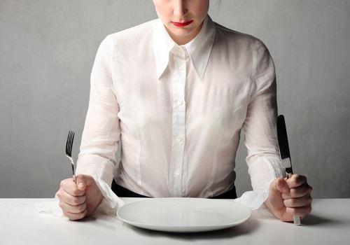 Девушка сидит за столом с тарелкой, ножом и вилкой