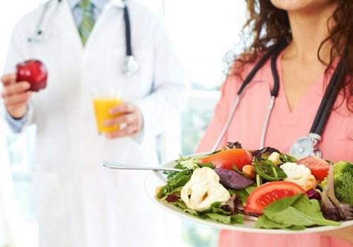 Врач держит тарелку с овощами
