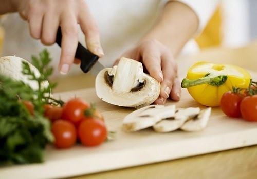 Женщина режет грибы