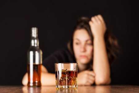 Женщина перед стаканом с алкоголем