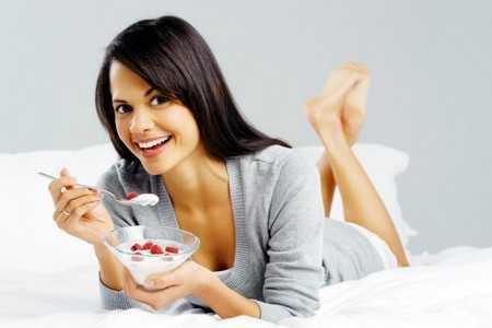 Женщина кушает творог с фруктами