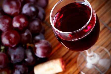 Бокал красного вина и виноград