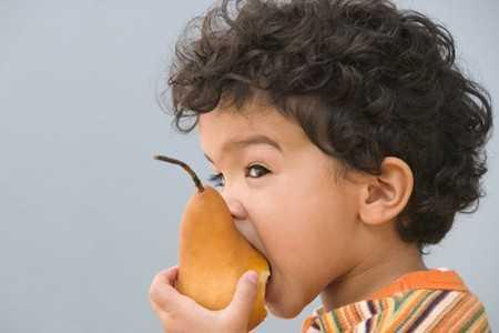Ребенок ест грушу