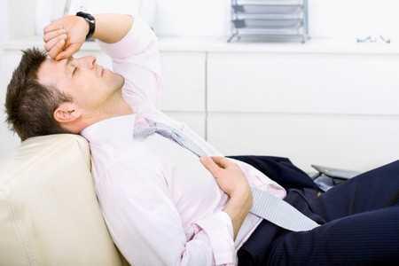 Уставший мужчина на диване